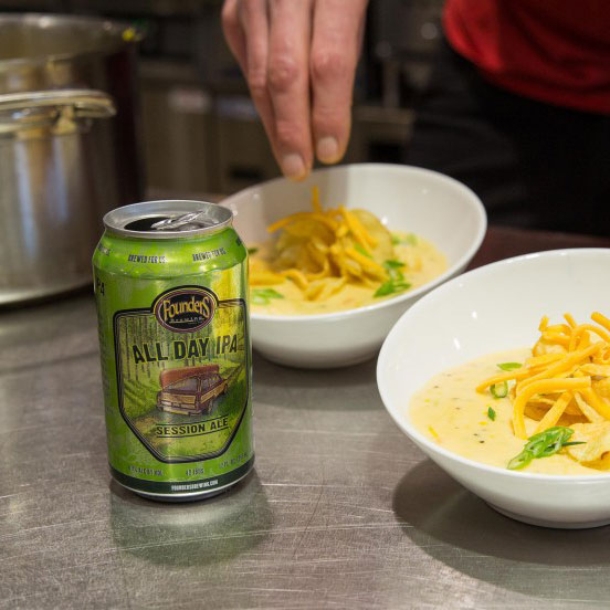 Man seasoning food with can of Founders All Day IPA