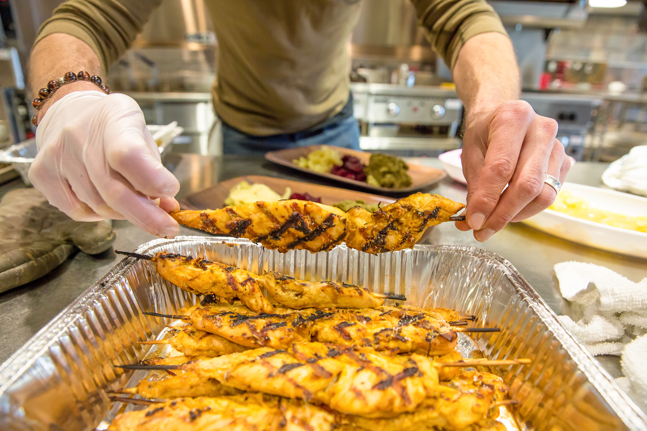 Person holding skewer of grilled chicken