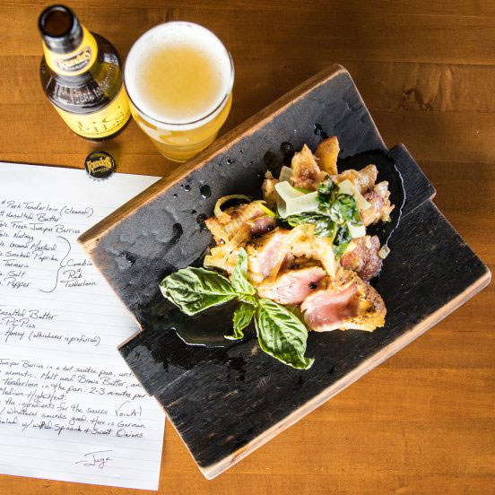 Pork tenderloin dish with bottle and glass of beer