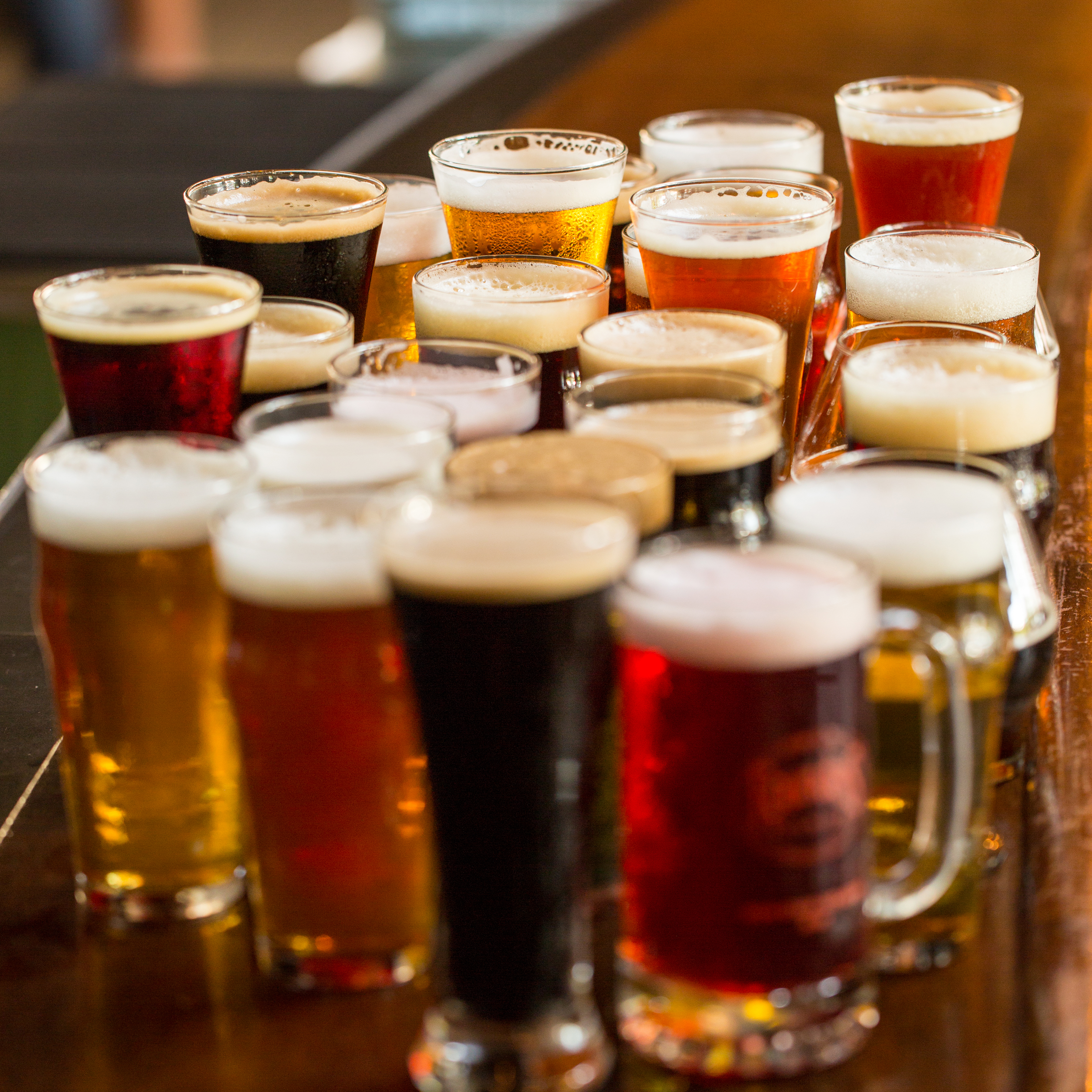 Many glasses of Founders beer crowded together on the bar
