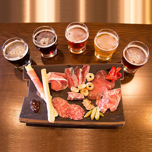 Ariel shot of Founders beer with a charcuterie board