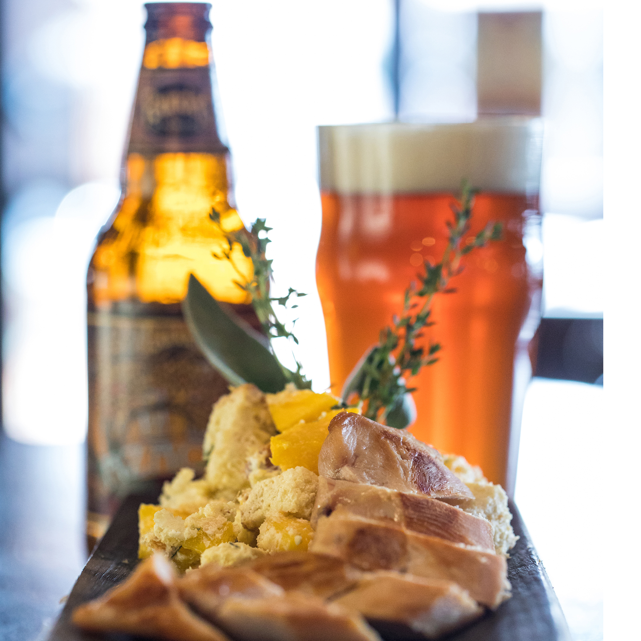Azacca Chicken recipe with chicken laid out on wooded platter with Founders beer in background