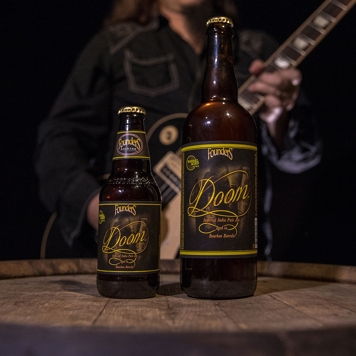 Two different sized bottles of Founders Doom sitting on beer barrel with guitar player in the background