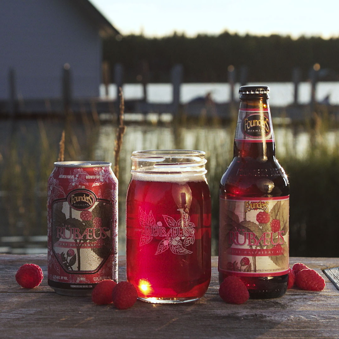 Founders Rubaeus bottle, can and glass on table outside by a lake and a pier