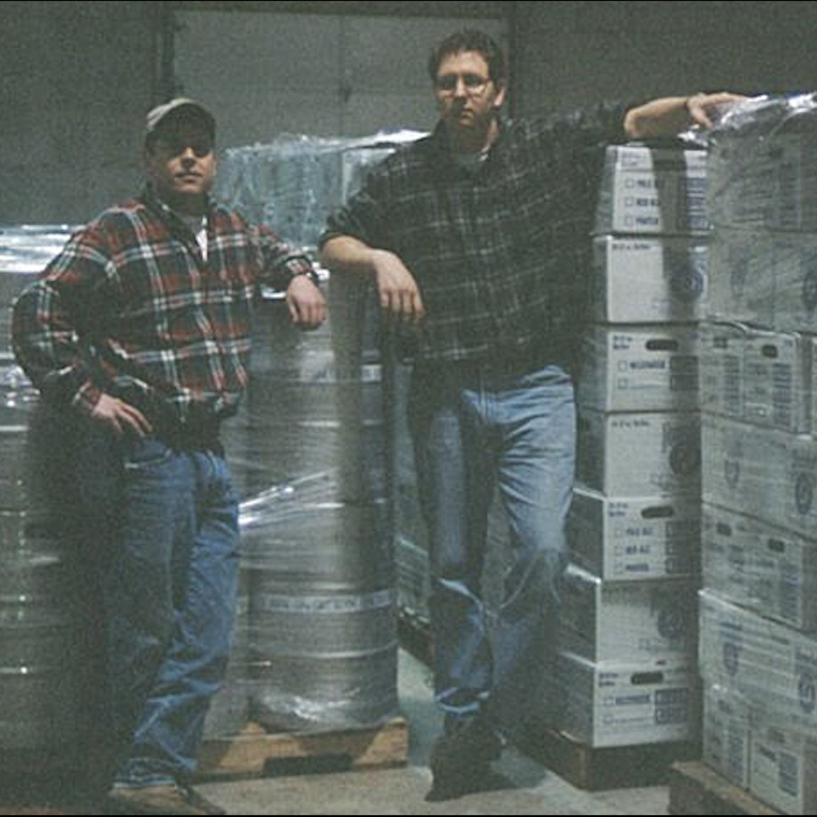 Two men with flannel shirts standing by kegs and cases of Founders beer