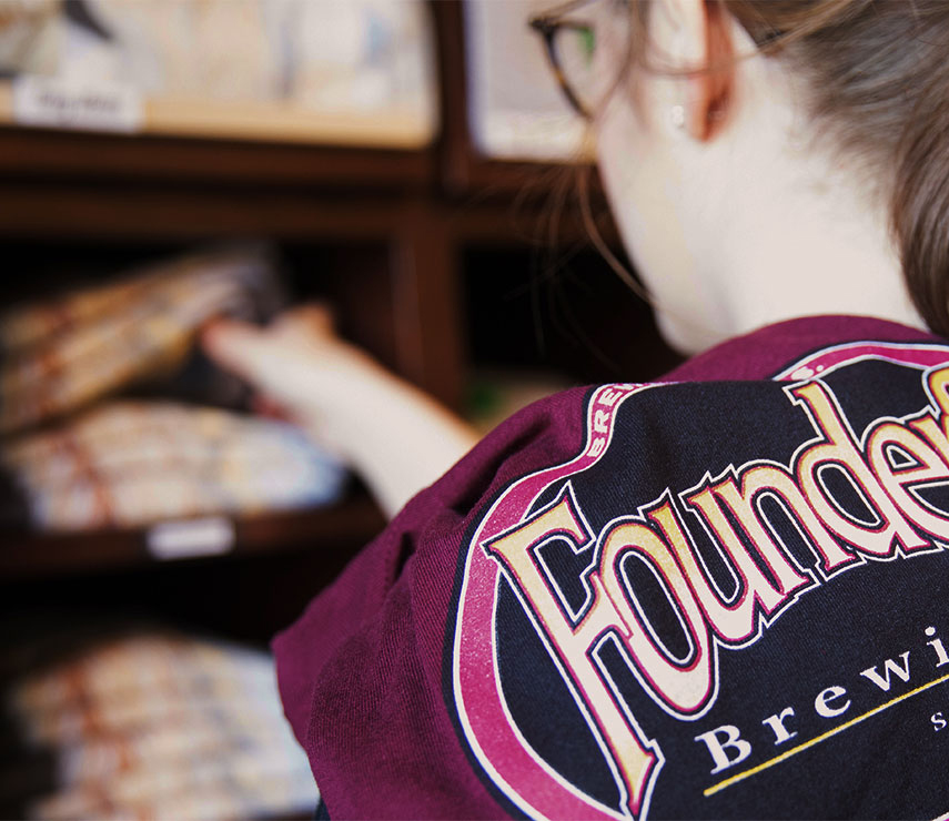 Woman folding Founders shirts at the Founders store