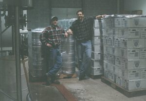 Two men, Dave and Mike, wearing flannel shirts standing by beer kegs and cases of beer