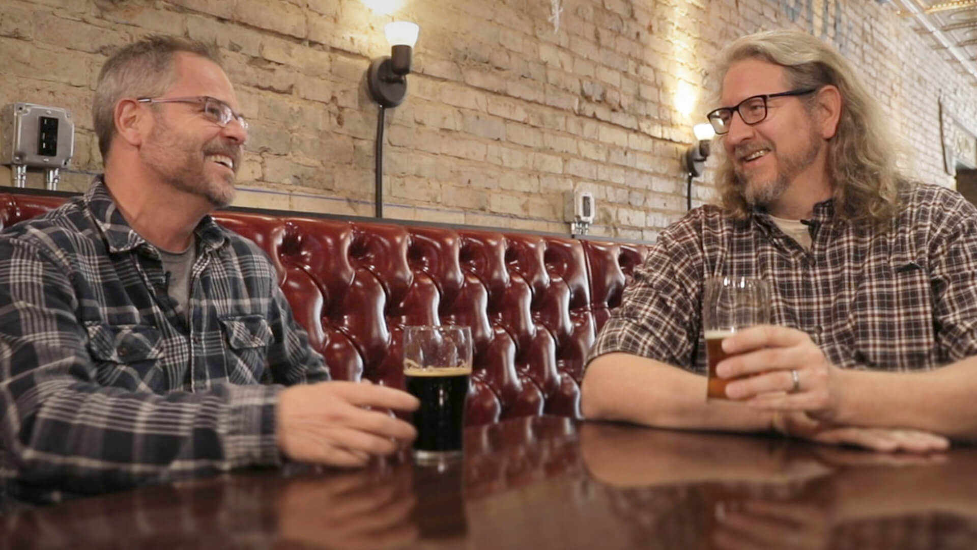 Two men in flannel shirts sitting in a booth together drinking beer and smiling