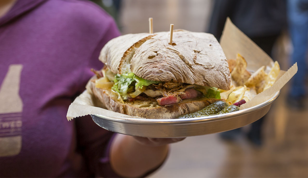 Woman in purple shirt holding a tray with a sandwich, pickles and fries on it
