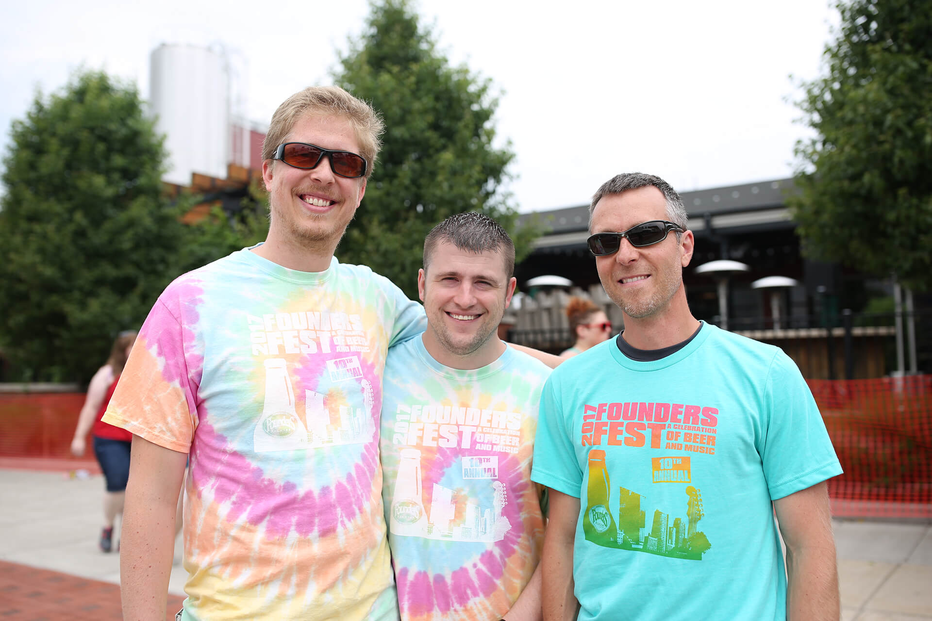 Three men smiling together wearing Founders Fest shirts