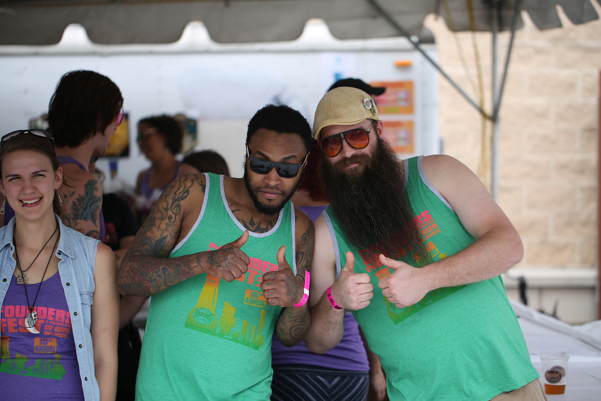 Two men wearing Founders Fest shirts giving thumbs up