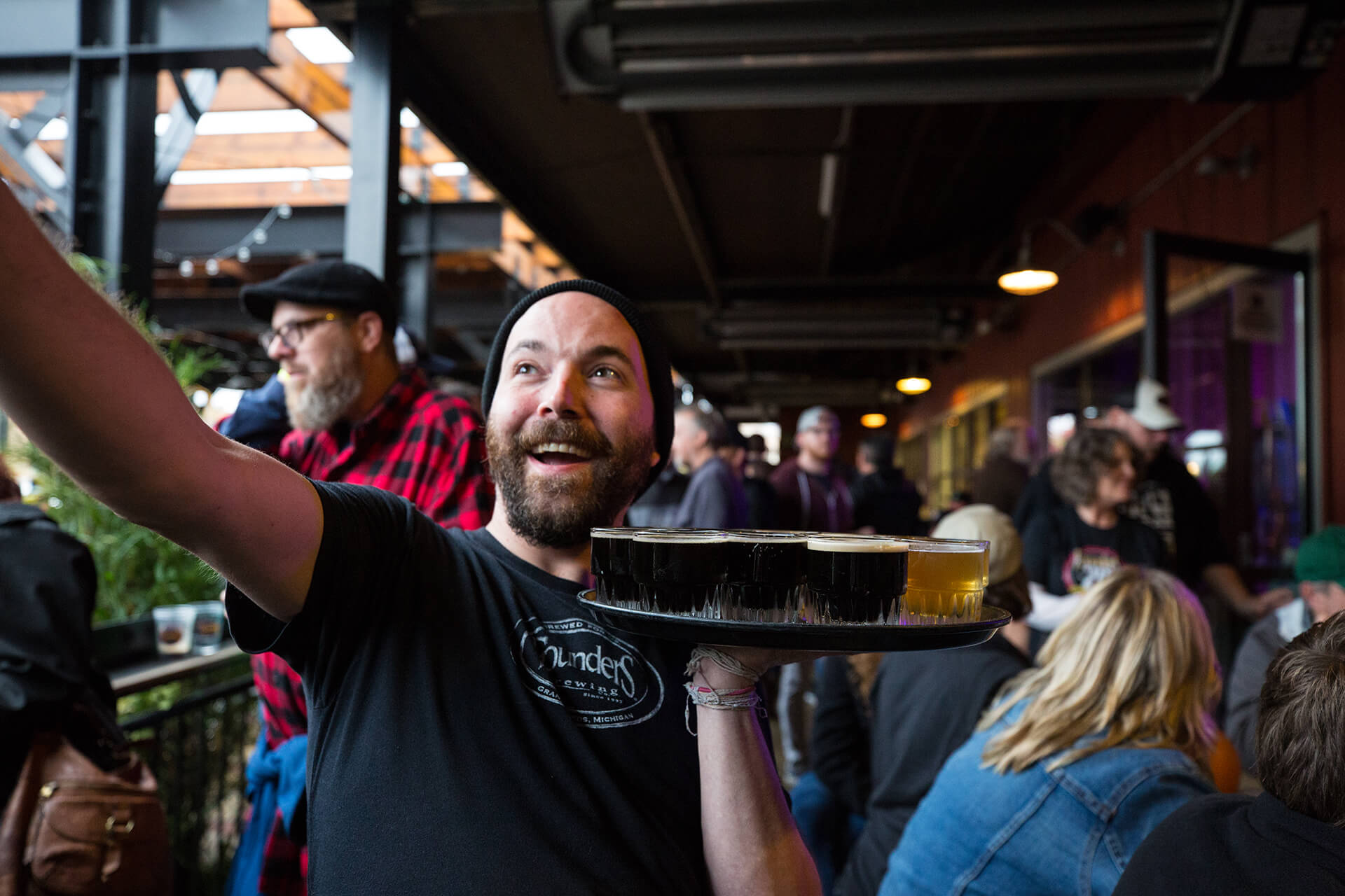 Bartender smiling with a tray full of beer with people at the taproom behind him