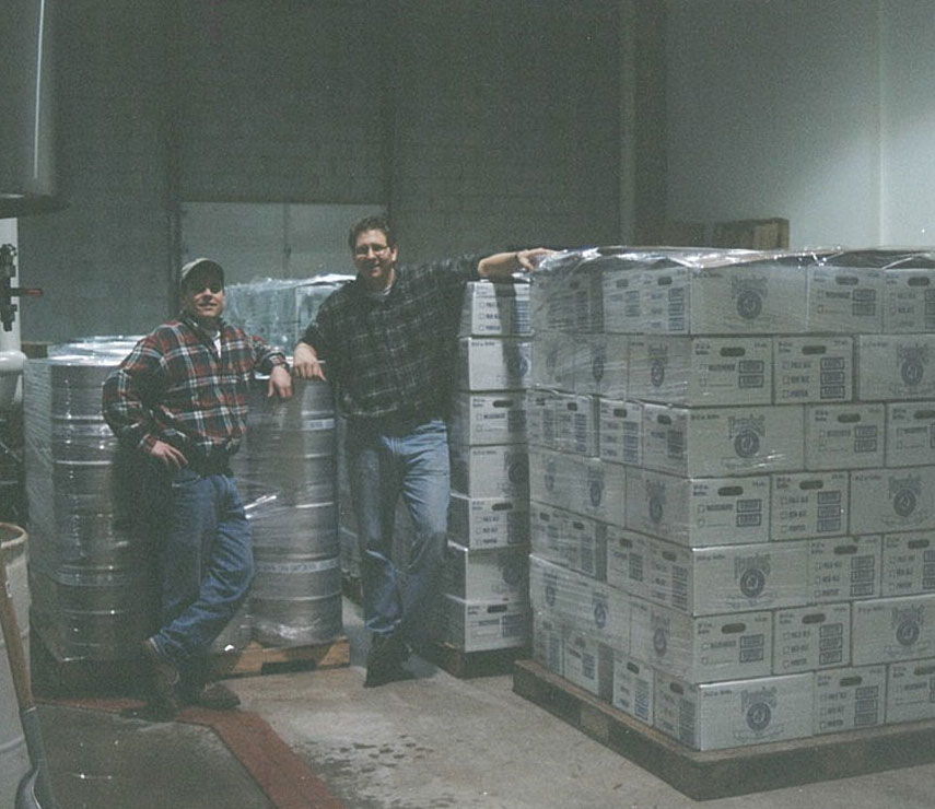 Two men in flannel shirts standing by beer kegs and cases of beer