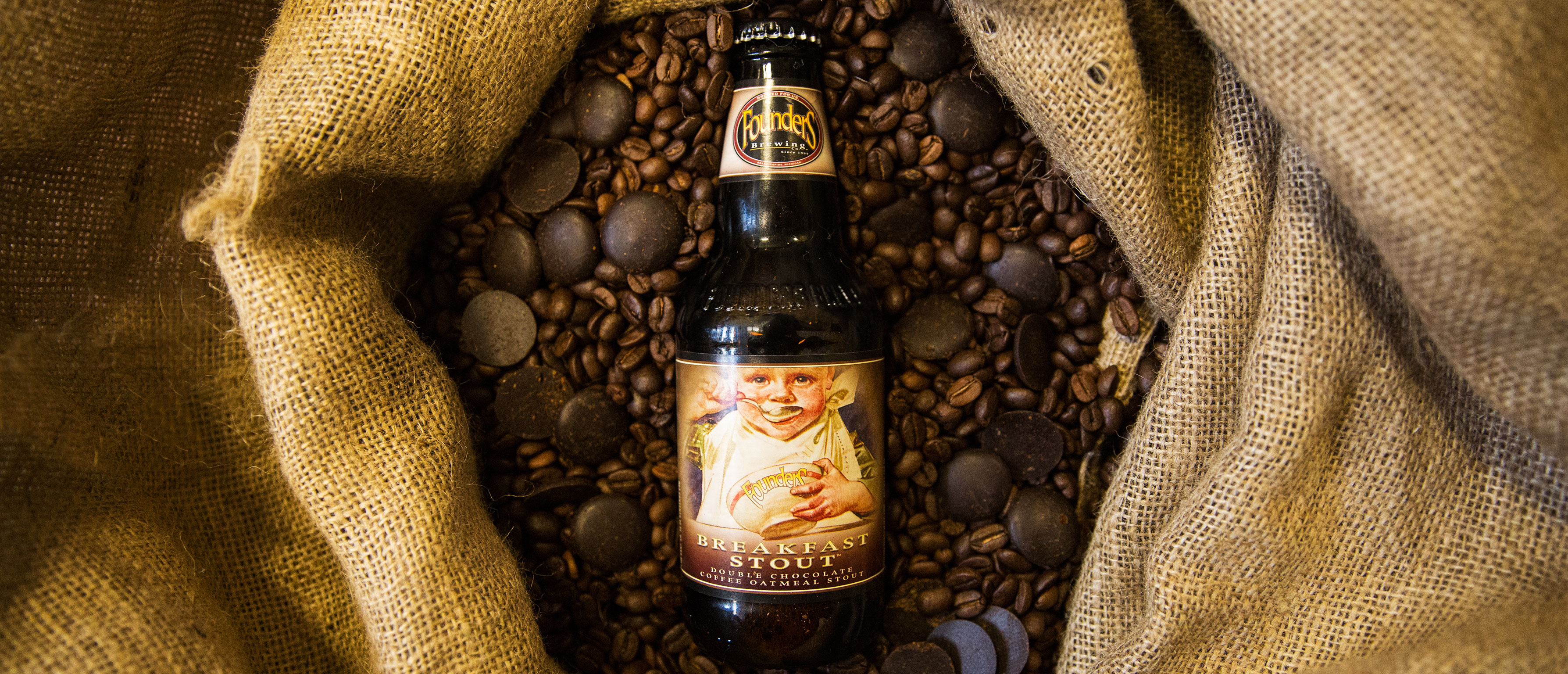 Founders Breakfast Stout bottle surrounded by chocolates and coffee beans