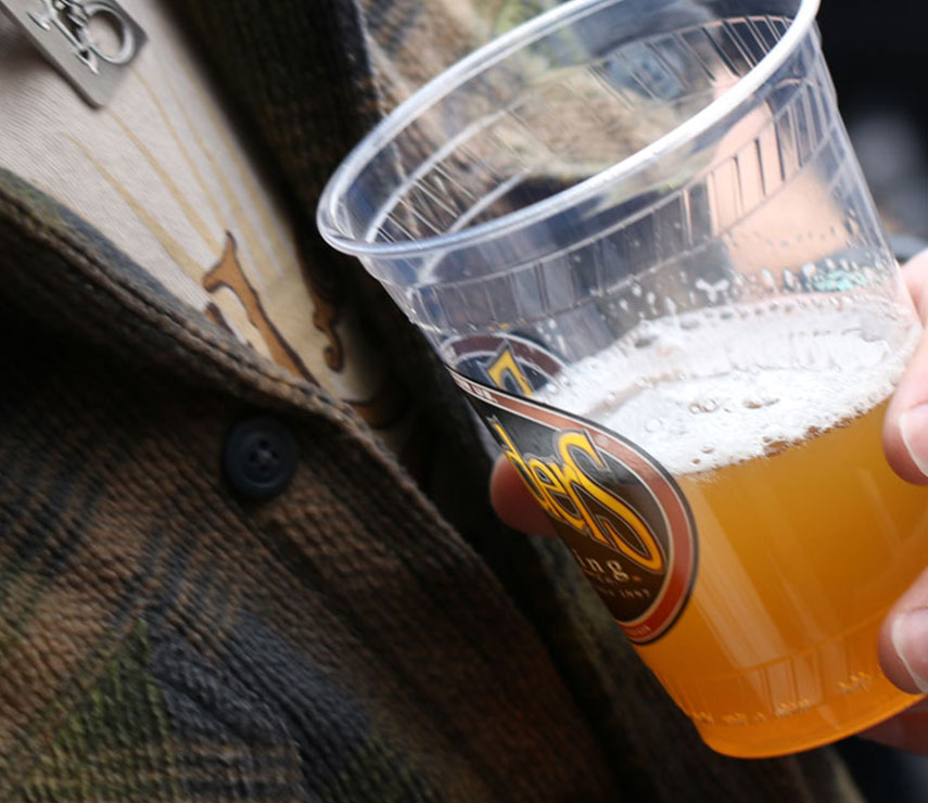 Close up of a person holding a Founders cup of beer