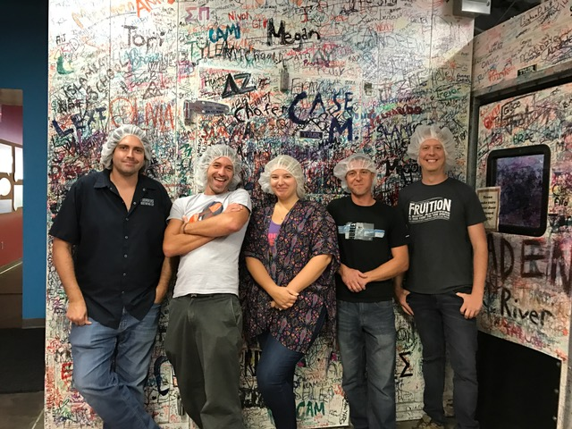 Group of people posing and smiling together, wearing hairnets
