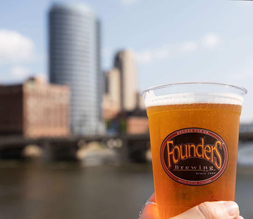 Founders cup with view of Grand Rapids behind it