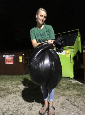 Woman in green shirt holding a trash bag