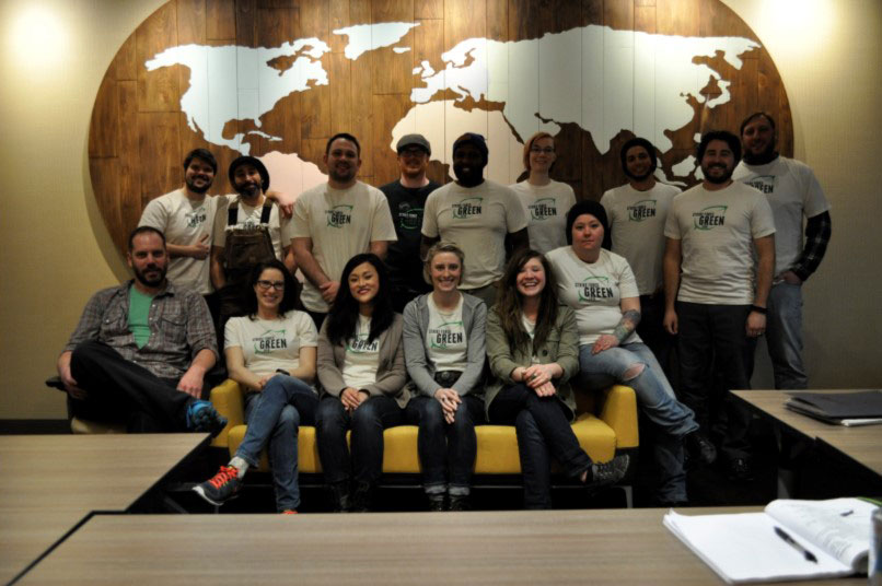 Group of people posing in front of a world map