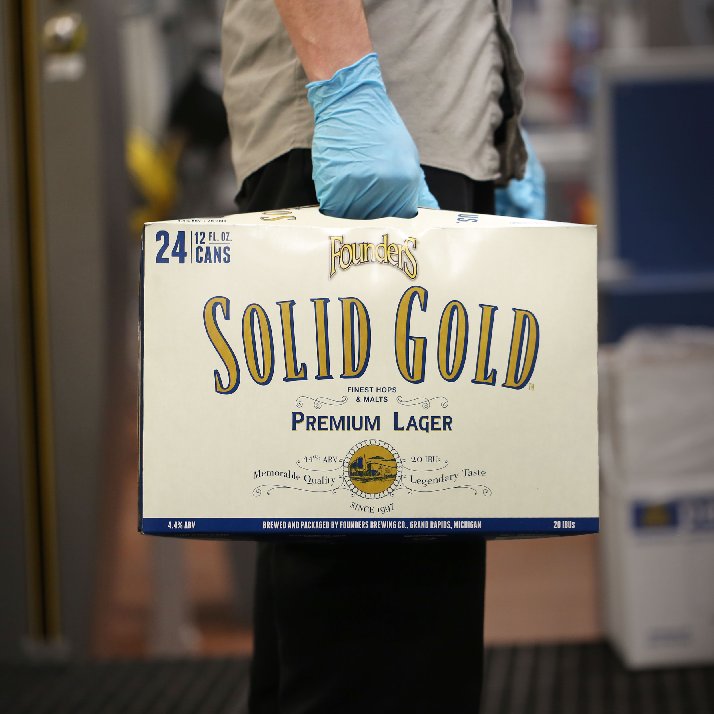 Man holding case of Founders Solid Gold