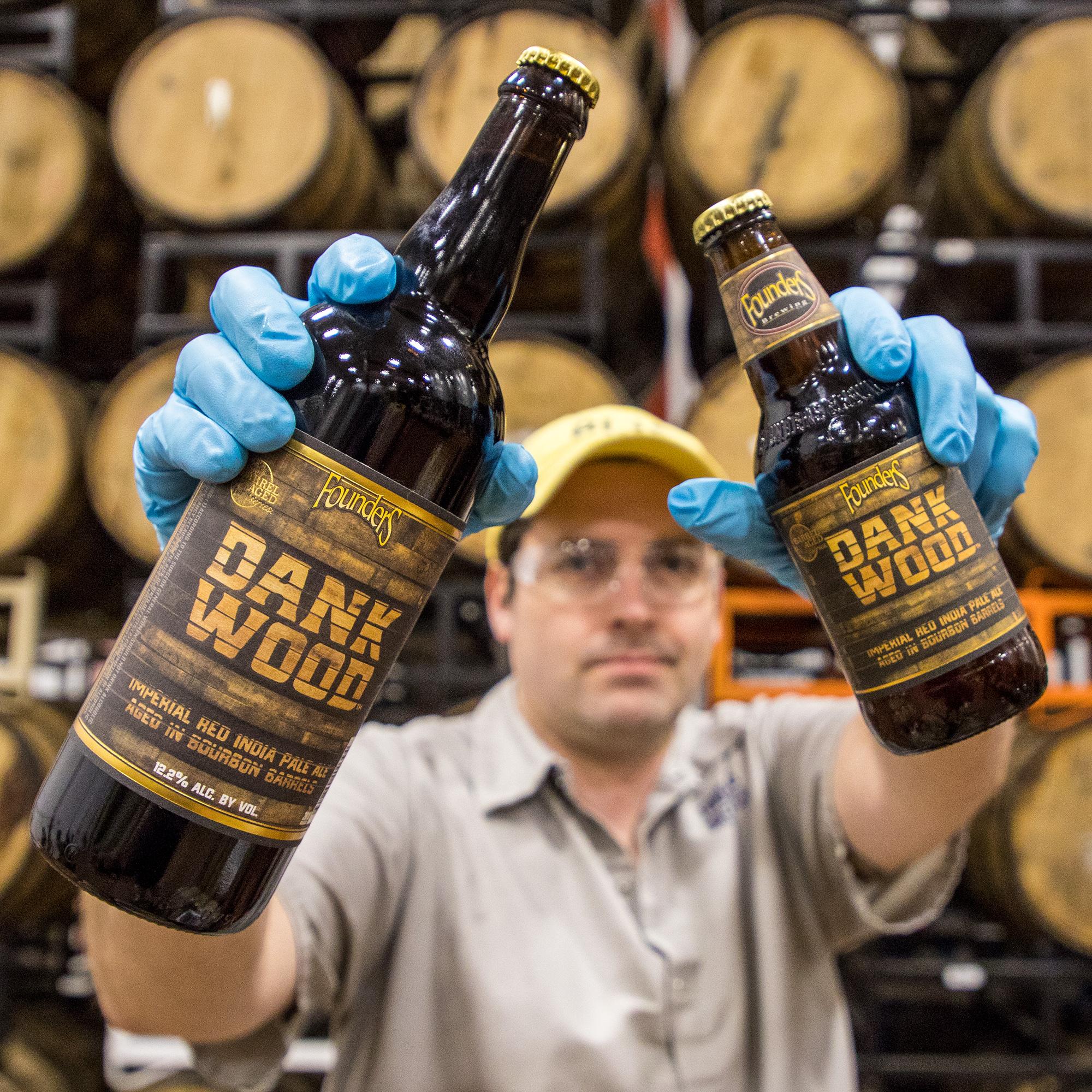 Man holding bottles of Founders Dank Wood