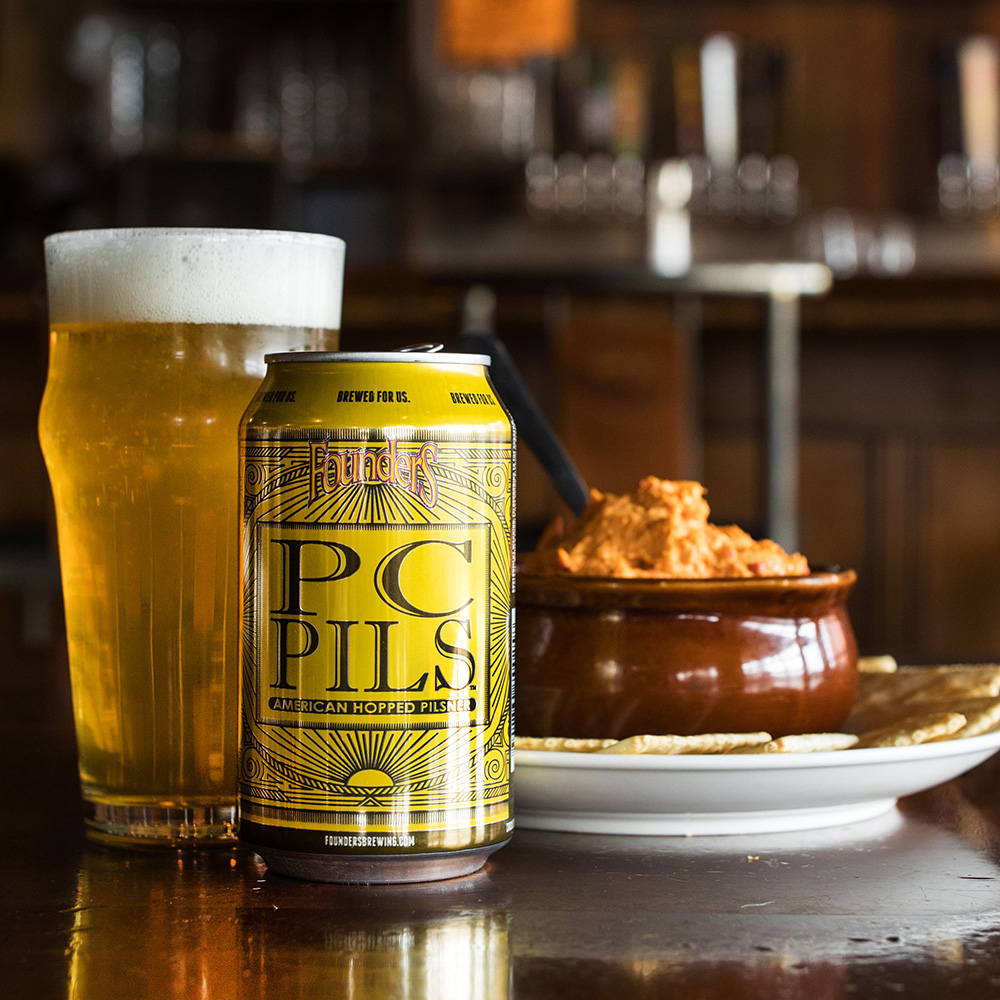 Can and glass of Founders Pc Pils and plate of crackers and dip