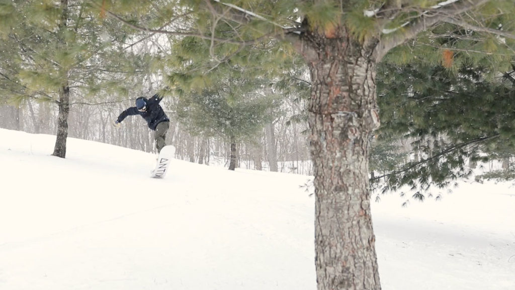 Man snowboarding in forest