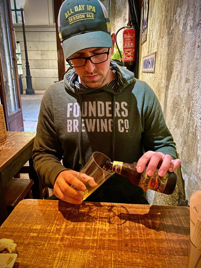 Man pouring Founders All Day IPA in beer glass
