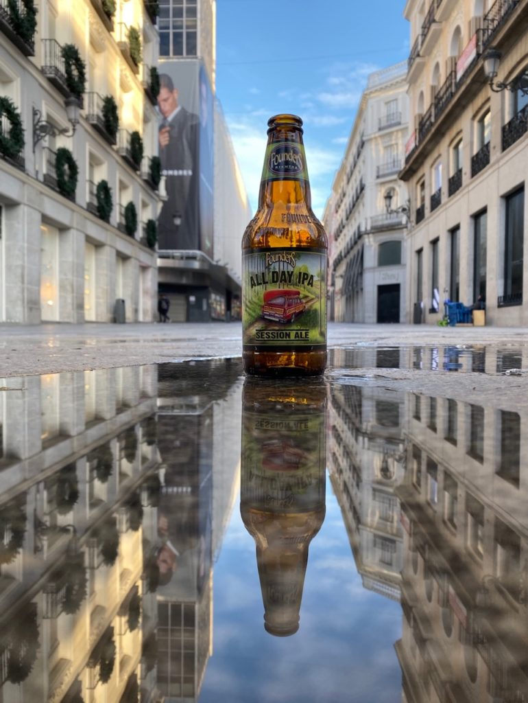 Bottle of Founders All Day IPA sitting sitting in puddle on street