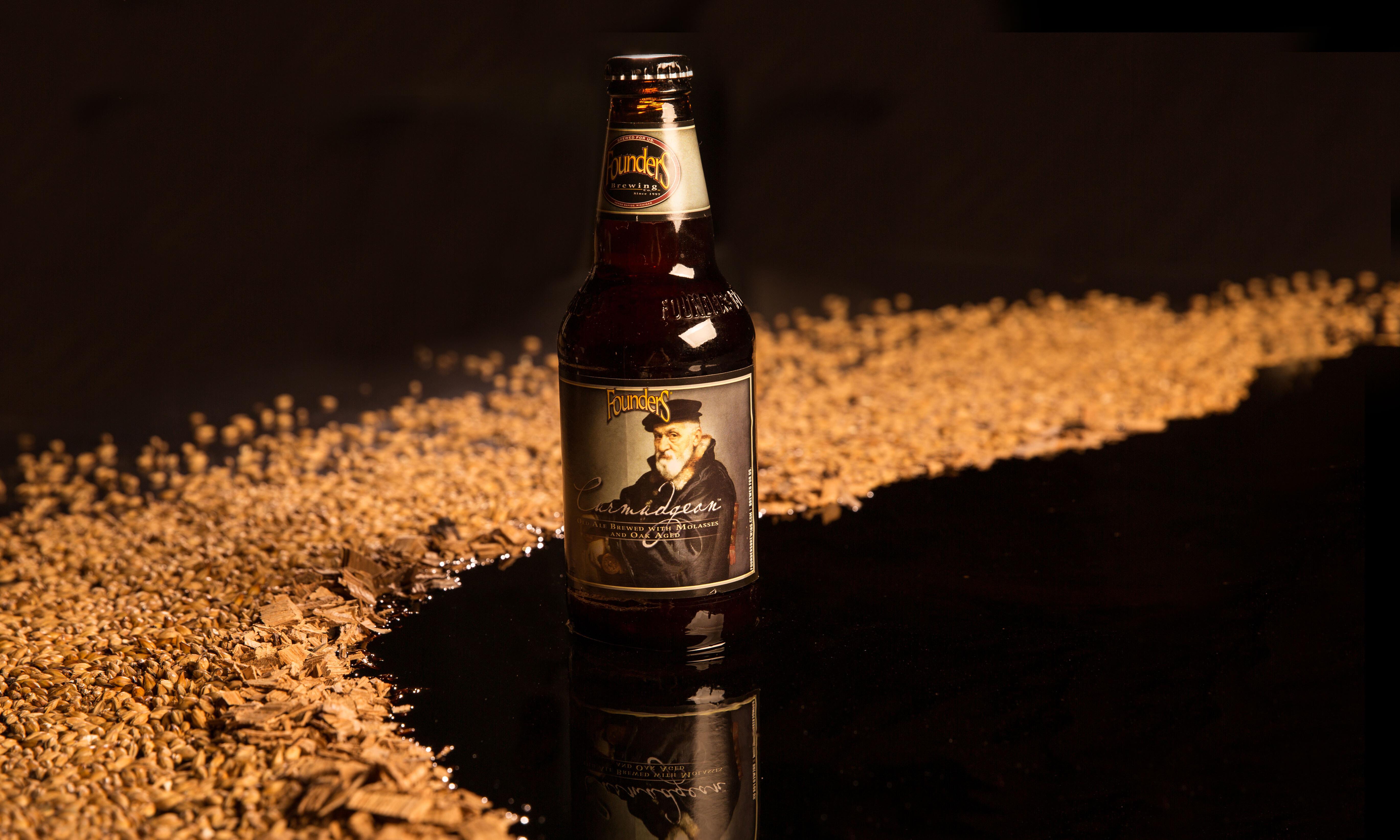 Bottle of Founders Curmudgeon sitting in oak chips