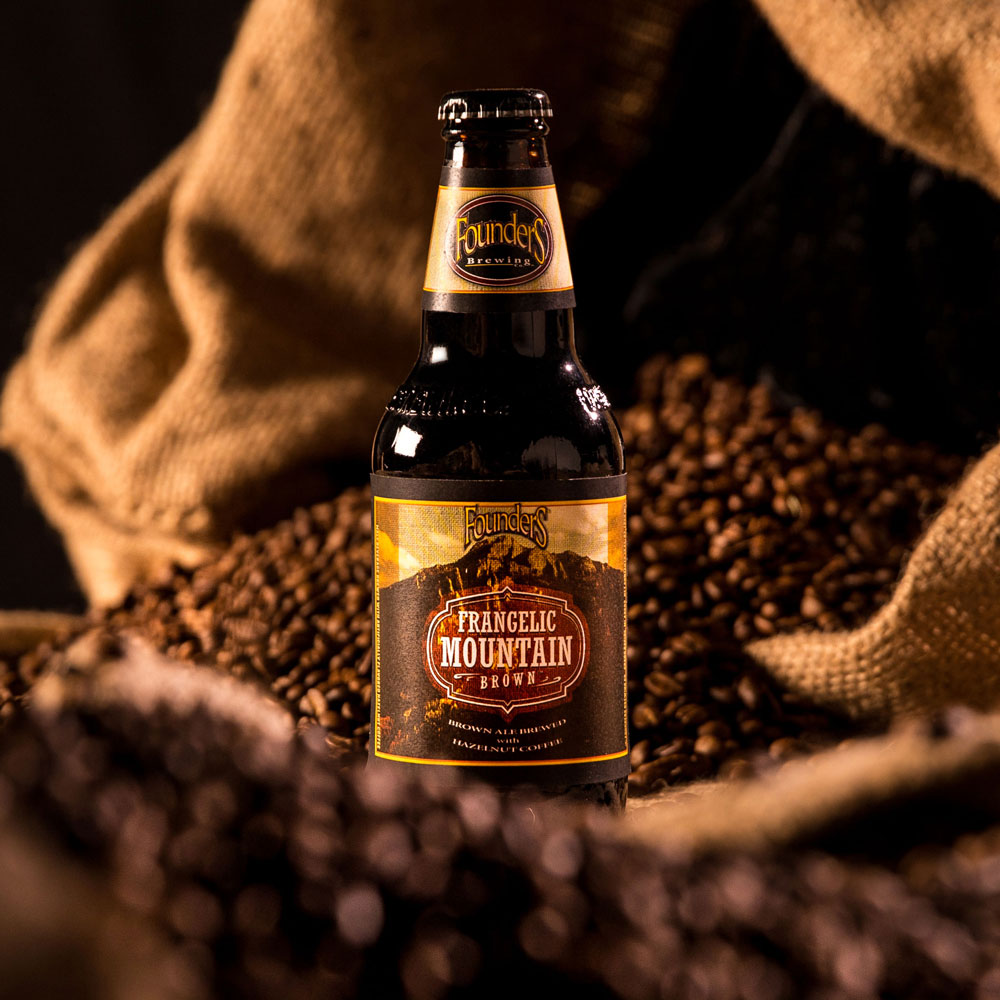 Bottle of Founders Frangelic Mountain Brown sitting in espresso beans