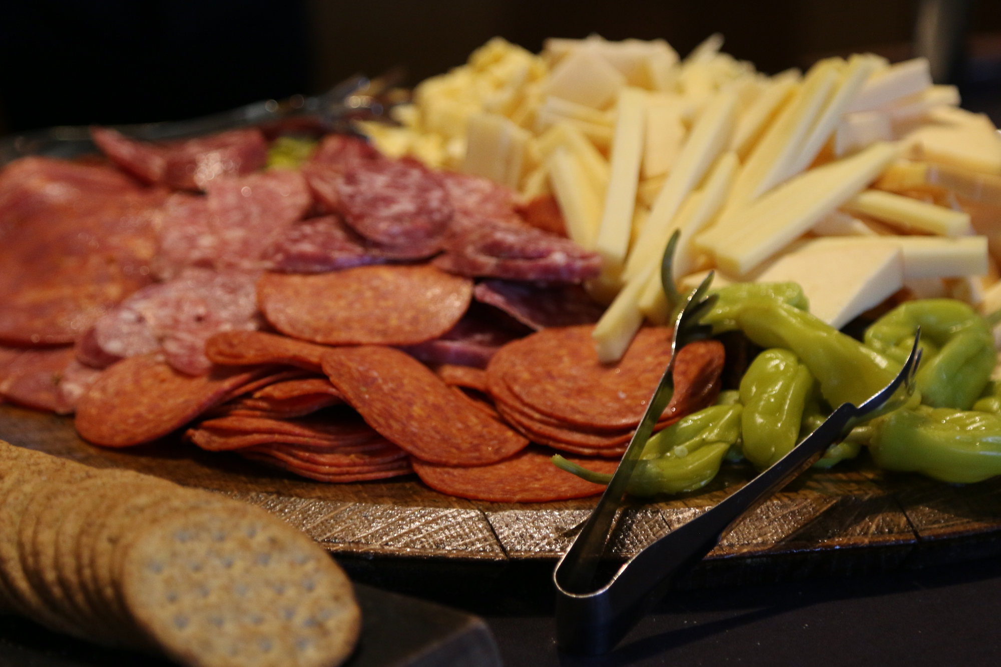 Charcuterie board with meats, cheeses, crackers, peppers