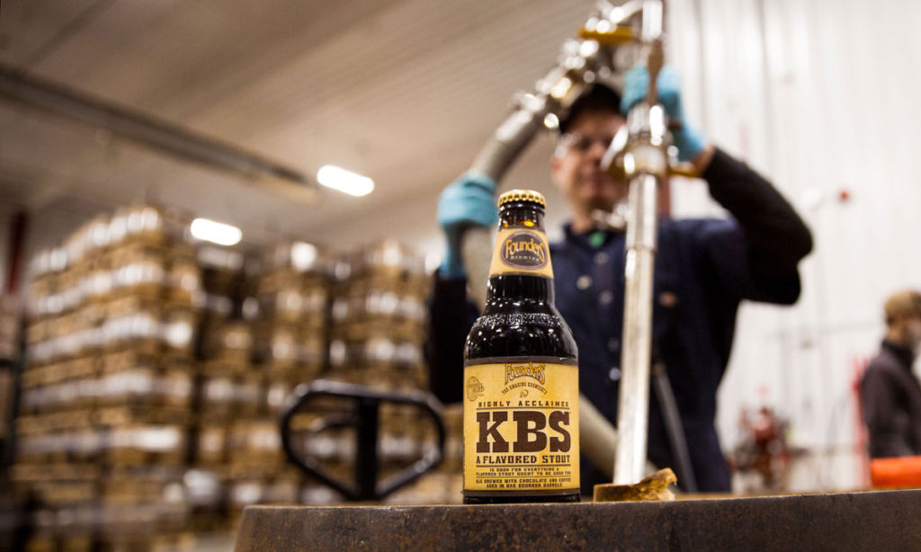 Man with a bottle of Founders KBS