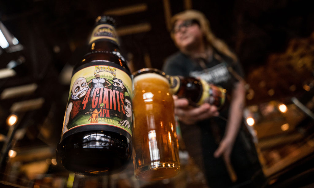 Women pouring Founders 4 Giants Indian Pale Ale into beer glass