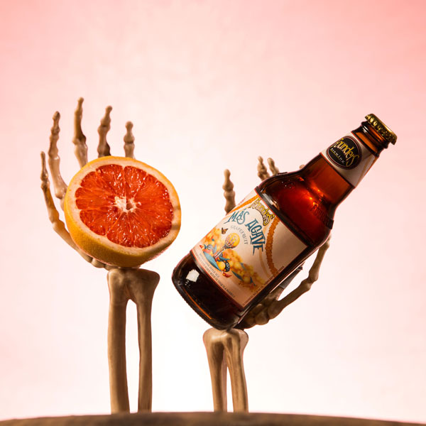 Skeleton hands holding a grapefruit and bottle of Founders Más Agave