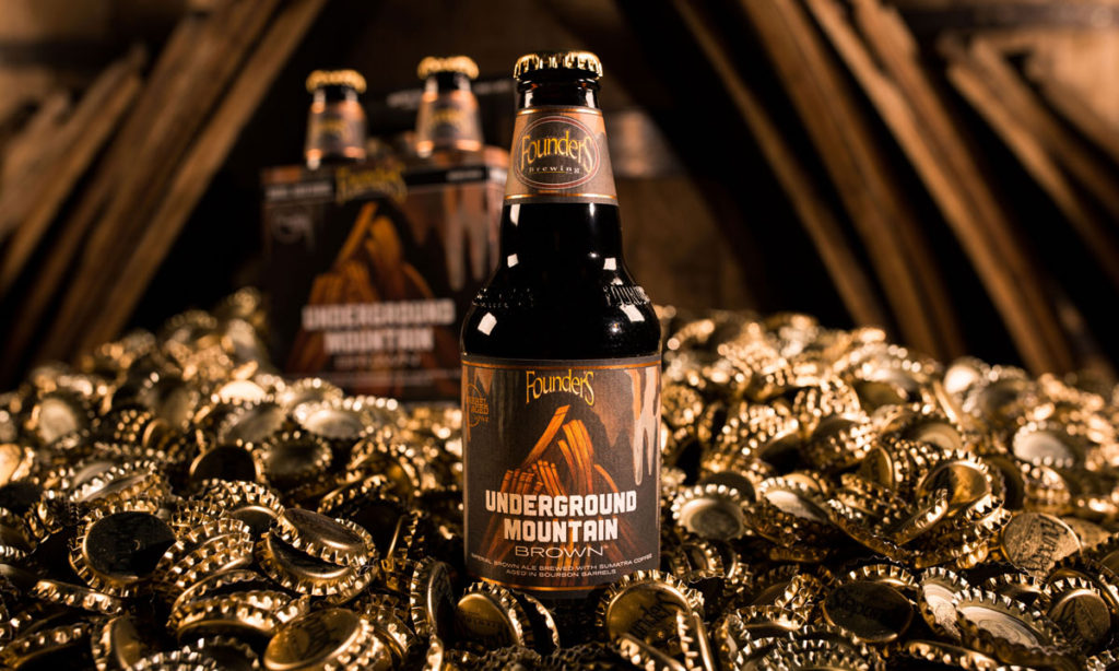 Underground Mountain Brown bottle in front of 4-pack among gold bottle caps