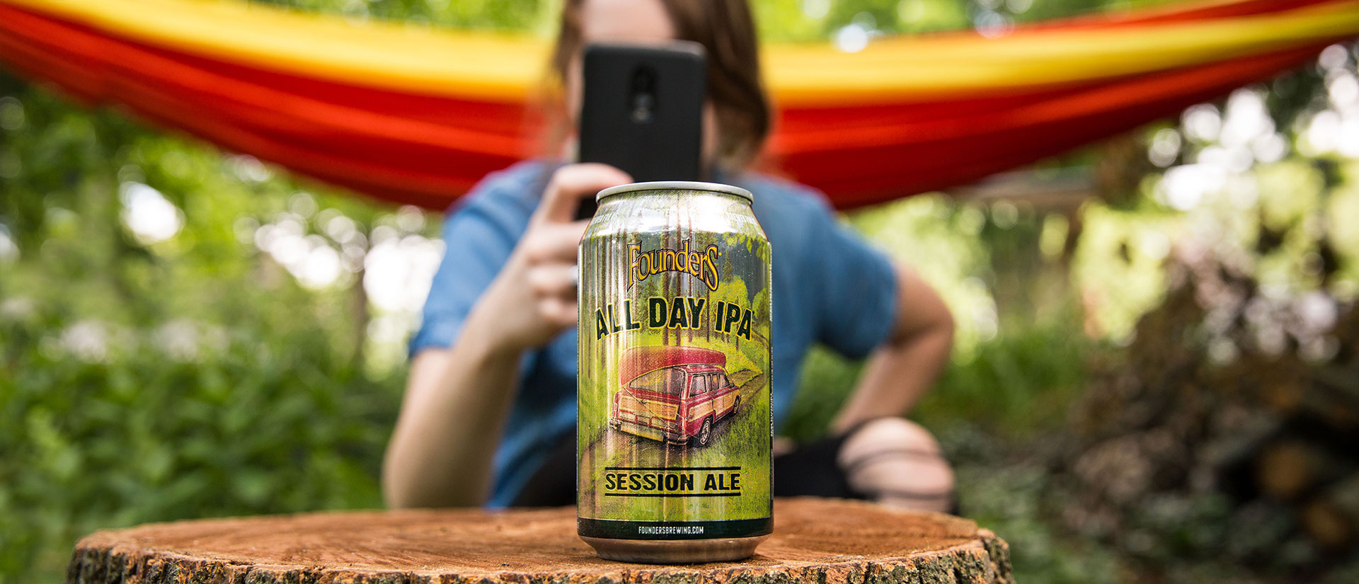 All Day IPA in front of woman taking a photo of it