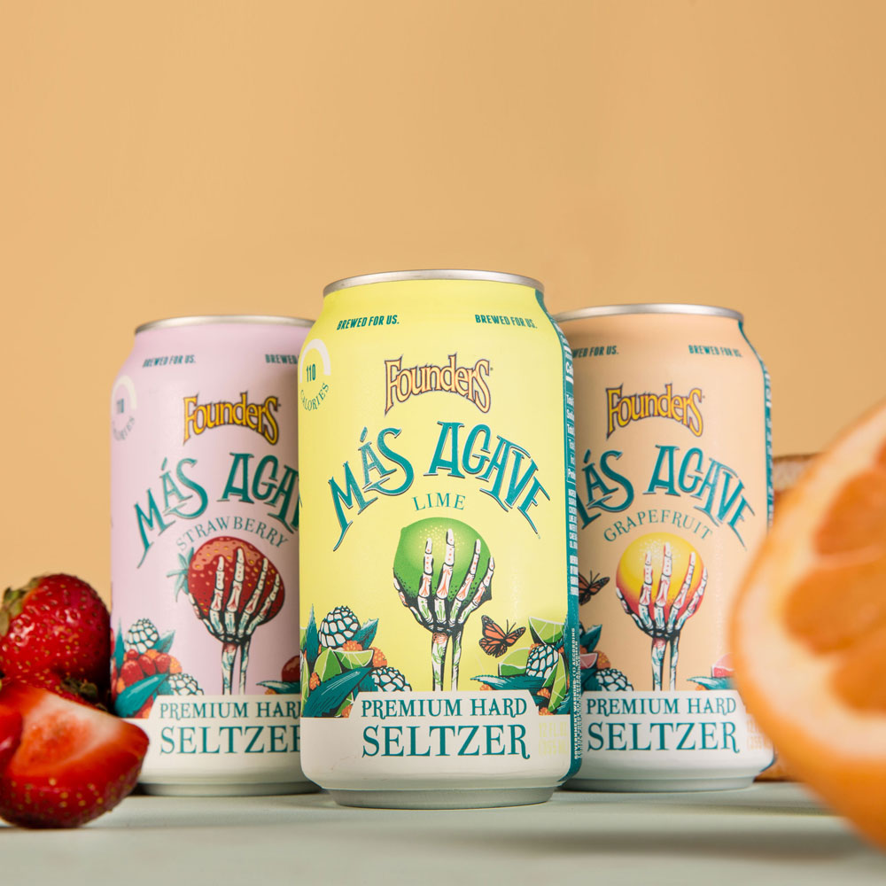 three cans of mas agave seltzer with fruit in foreground