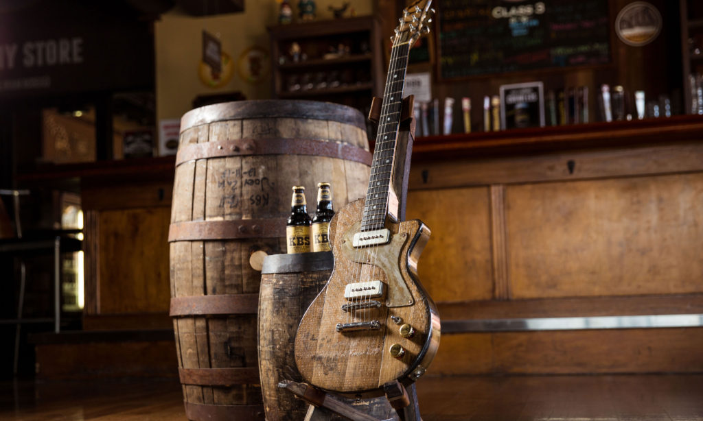 kbs barrel stave guitar next to barrels with two KBS bottles