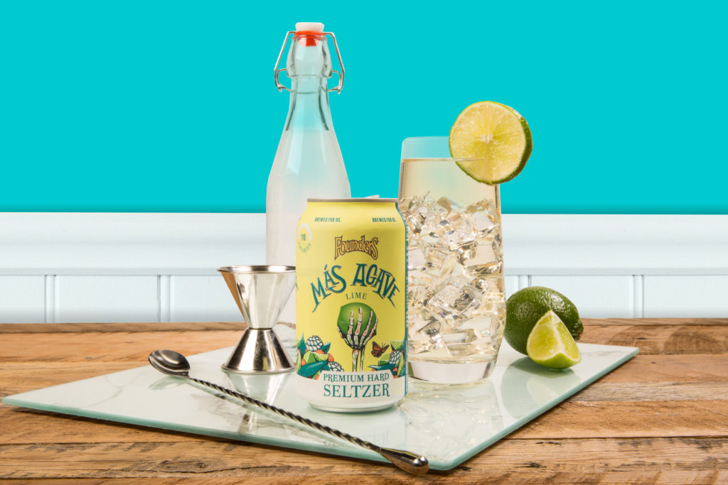 Can of Mas Agave Seltzer with gin and tonic and various cocktail accessories
