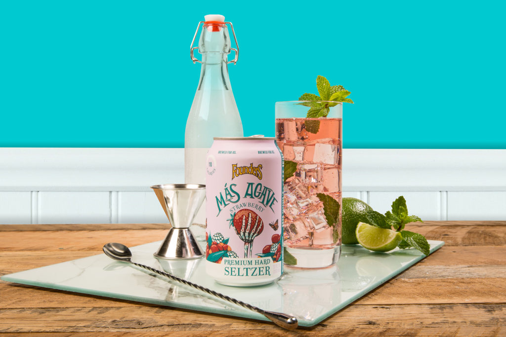 Can of Mas Agave Seltzer with mojito cocktail and various cocktail accessories