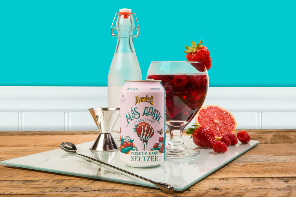 Can of Mas Agave Seltzer with glass of sangria and various cocktail accessories