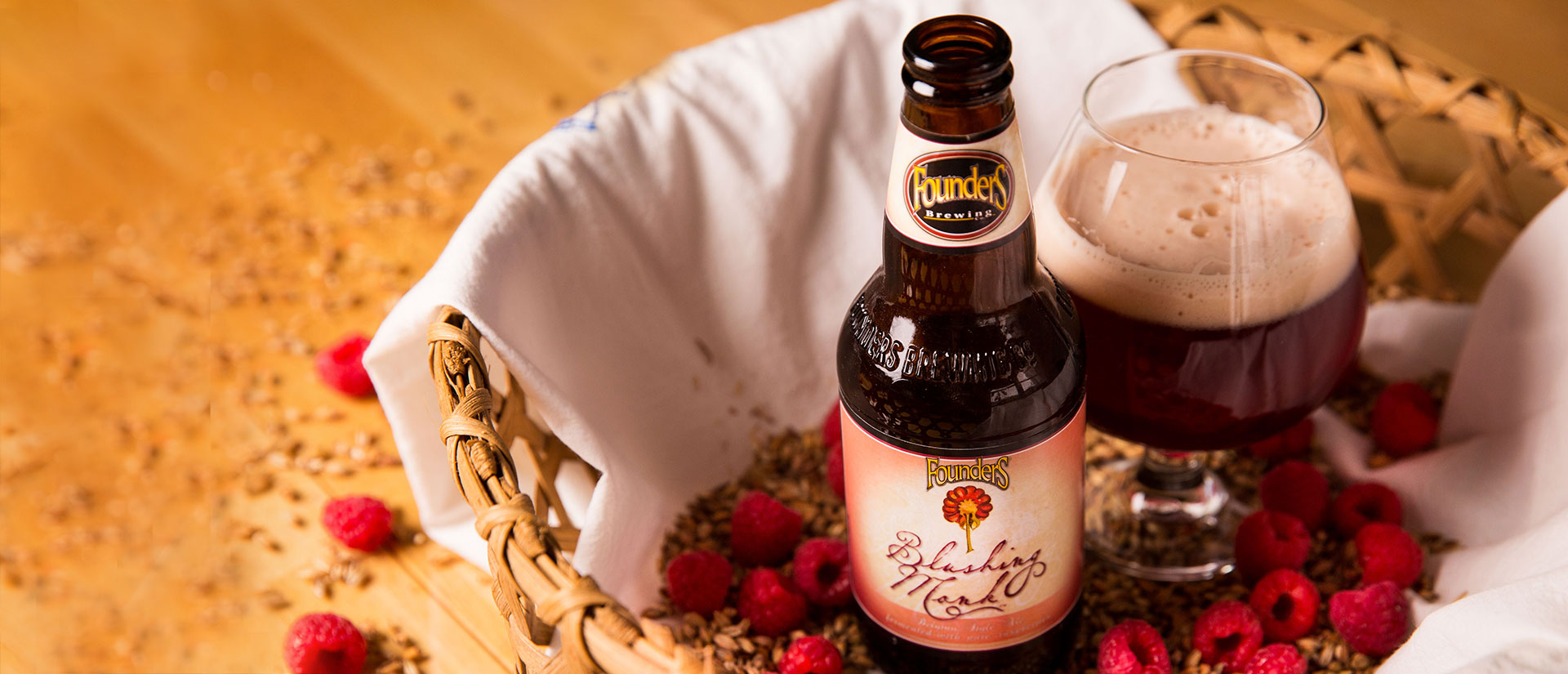 blushing monk bottle and snifter pour in a basket filled with raspberries