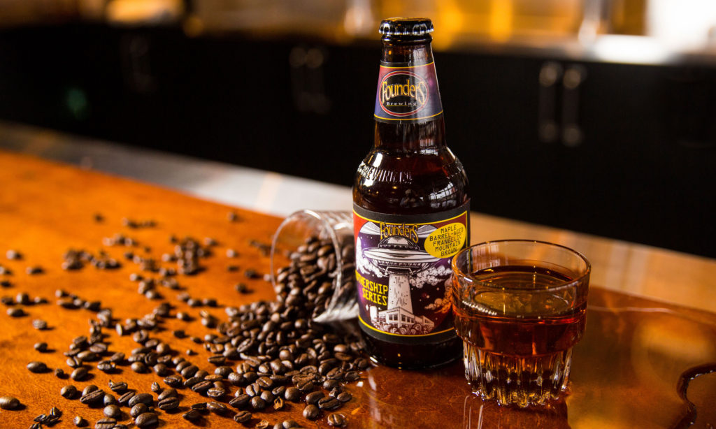 Maple Barrel Aged Frangelic Mountain Brown Bottle next to scattered coffee beans and a shot glass filled with an amber-hued beer
