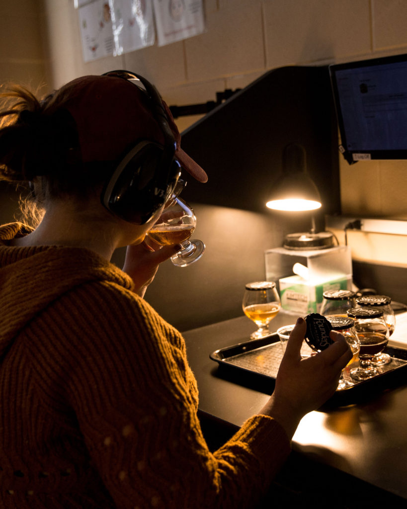 person wearing headphones sipping beer from snifter under dim light in a lab setting