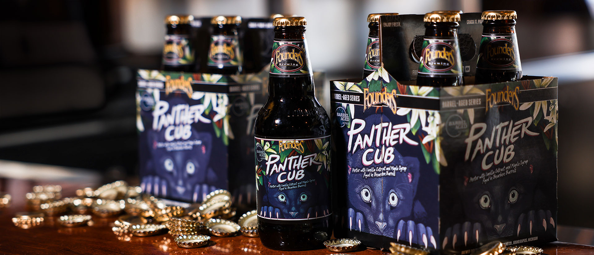 Panther Cub 12oz bottle and 4-packs with scattered gold bottle caps