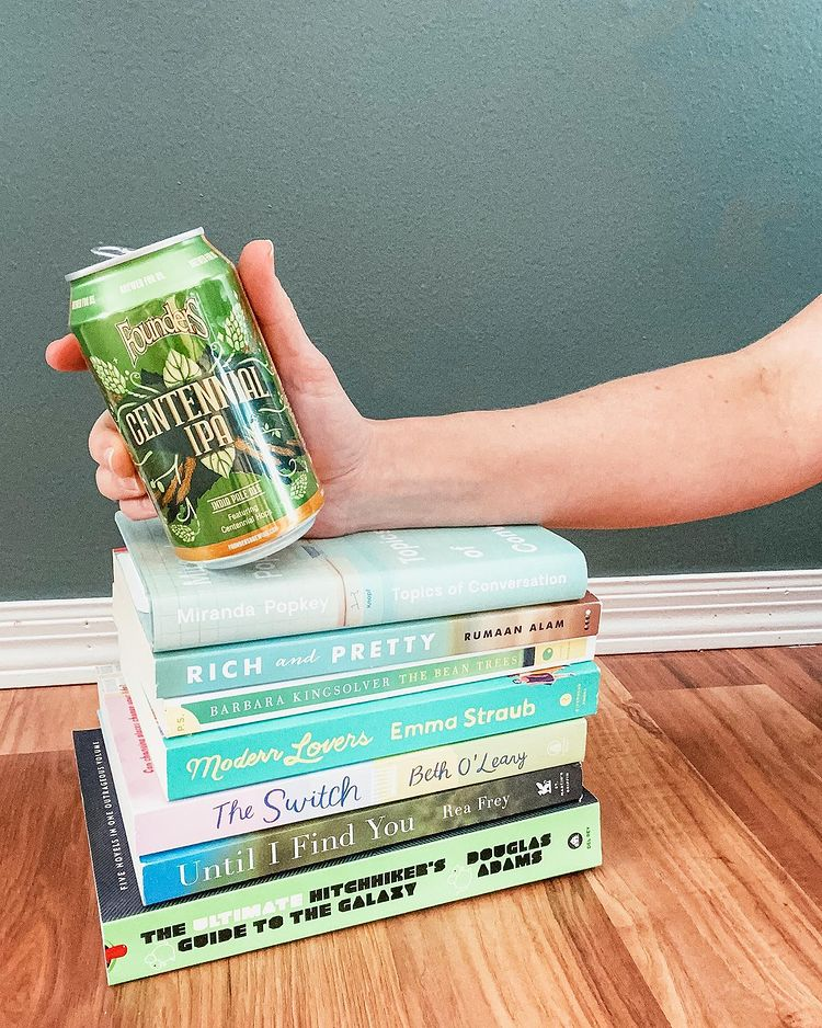 A hand holding a can of Centennial IPA on top of a stack of green books.