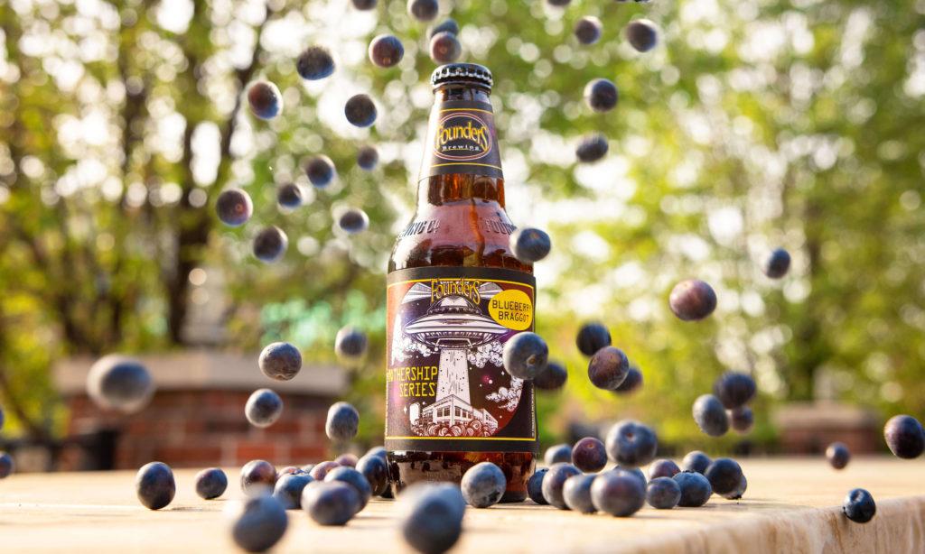 blueberry braggot bottle with blueberries falling around it