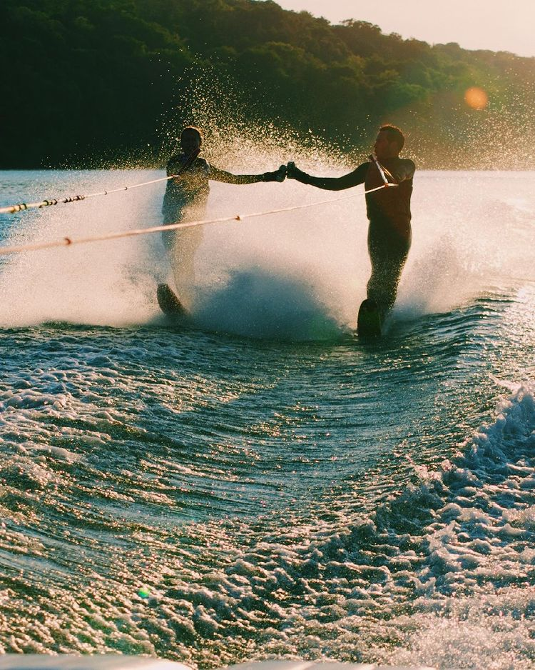 Two people cheersing while water skiing.