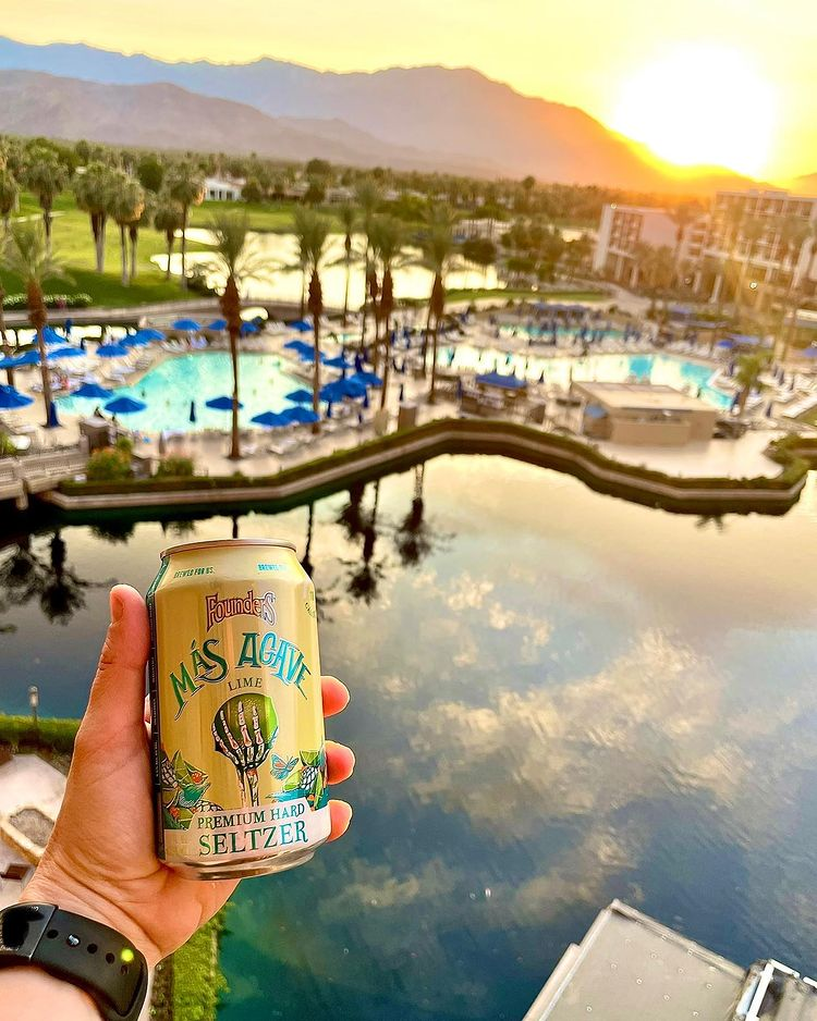 A hand holding a can of Mas Agave Premium Hard Seltzer in front of the water.